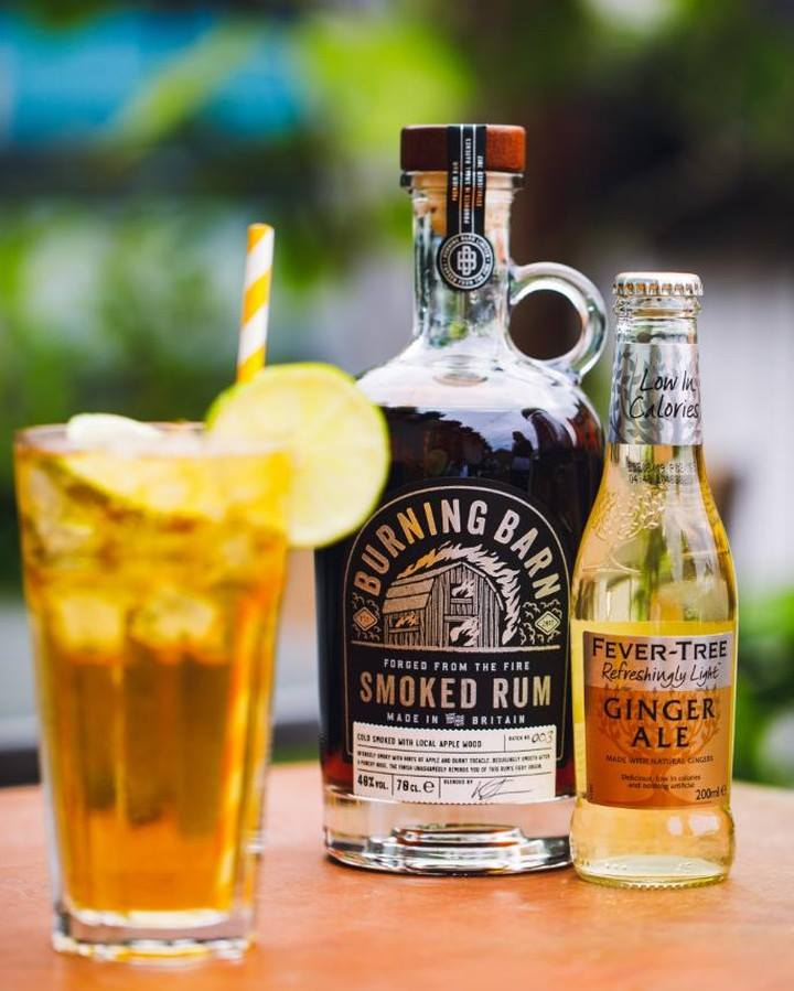 Smoked Rum and ginger ale cocktail with straw