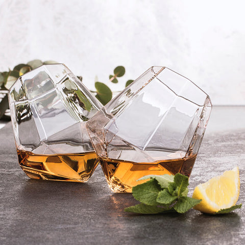 Pair of diamond shaped glasses filled with whiskey drink