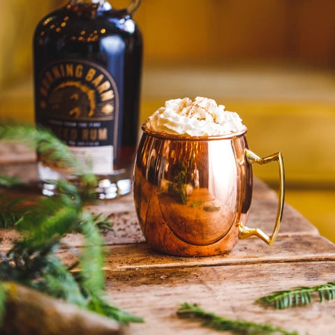 Hot chocolate in gold mug with whipped cream