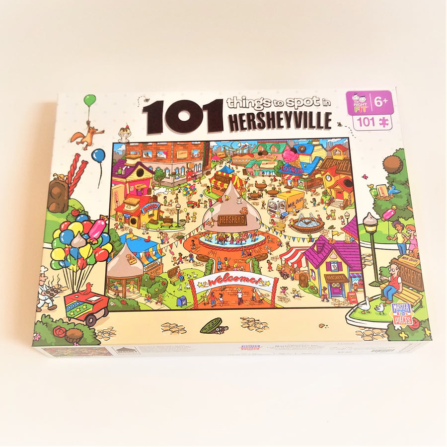 Puzzle box cover for 101 things to spot  in Hersheyville featuring the amusement park. Colorful balloons and street scene  surround the square  outside the park.