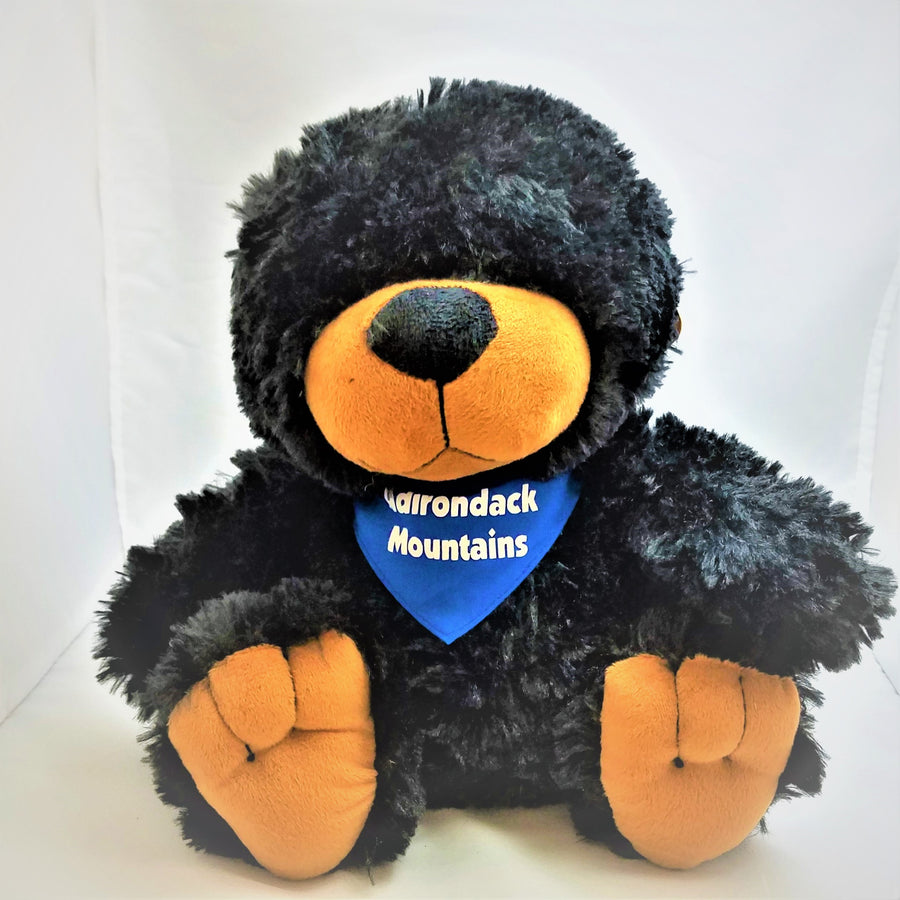 Full stuffed black bear in sitting position with blue neckerchief with white type that reads Adirondack Mountains