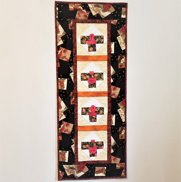 Rectangular quilted wall hanging with Asian theme in center. Black border with maroon and brown squares of pattern. Center  4 squares off white and white pattern with kimono in center of each. Red sash and collar on a dark cloth with flower pattern on each.
