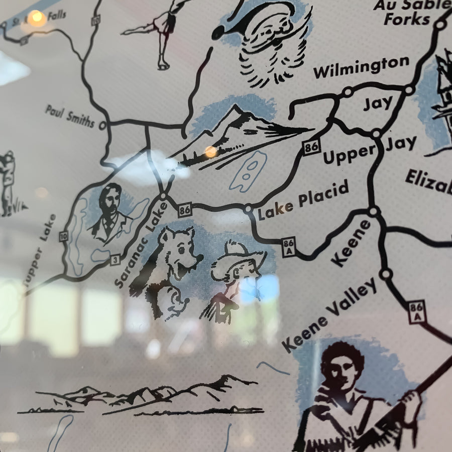 close up of map inset with black lines delineating and drawings of people and animals.