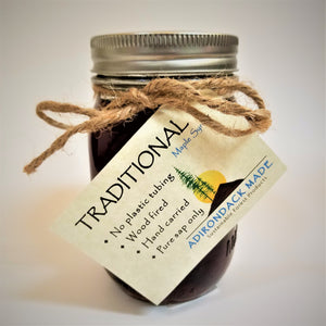 Mason jar of pure maple syrup with gold lid, rope tie with off-white card attached with lettering describing the TRADITIONAL Maple Syrup within from Adirondack Maple