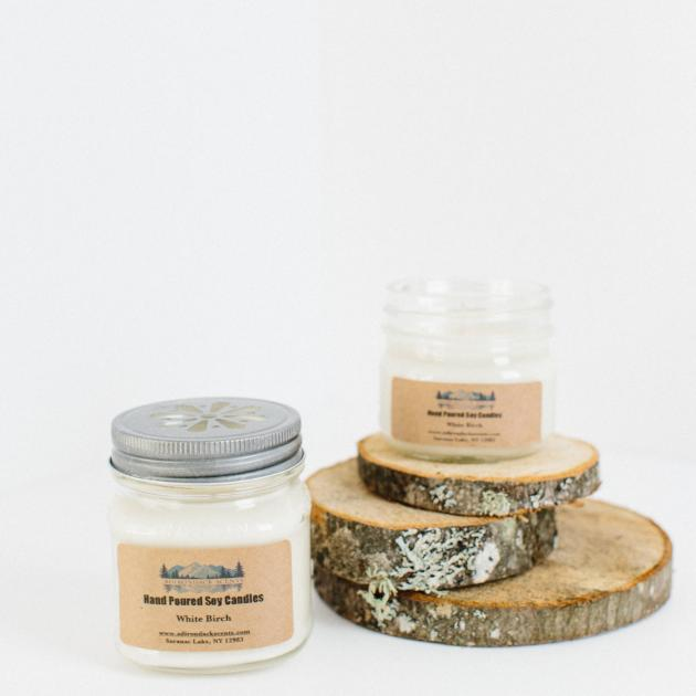 Left to right, jarred candle with silver lid, beige manufacturer's label with hint of white candle within. On 3 birch bark clabs sits an open candle jar. The manufacturer's label is displayed on the front of the open jar.