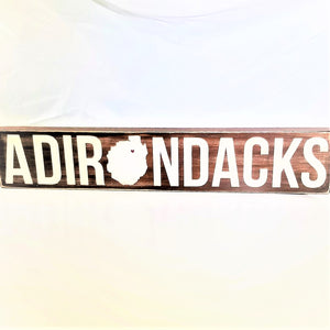 Brown horizontal sign with white lettering of the word Adirondacks. The O in the middle is in the shape of the Adirondack Park with a red heart in the upper portion.