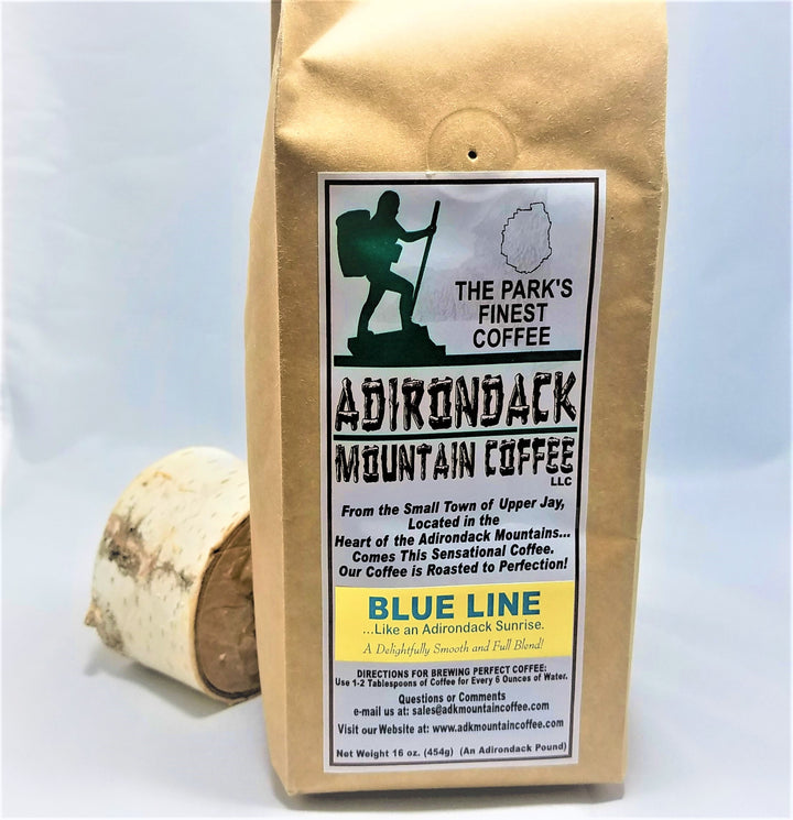 A package of Blue Line Coffee from Adirondack Mountain Coffee standing upright in front of a slice of birch wood.