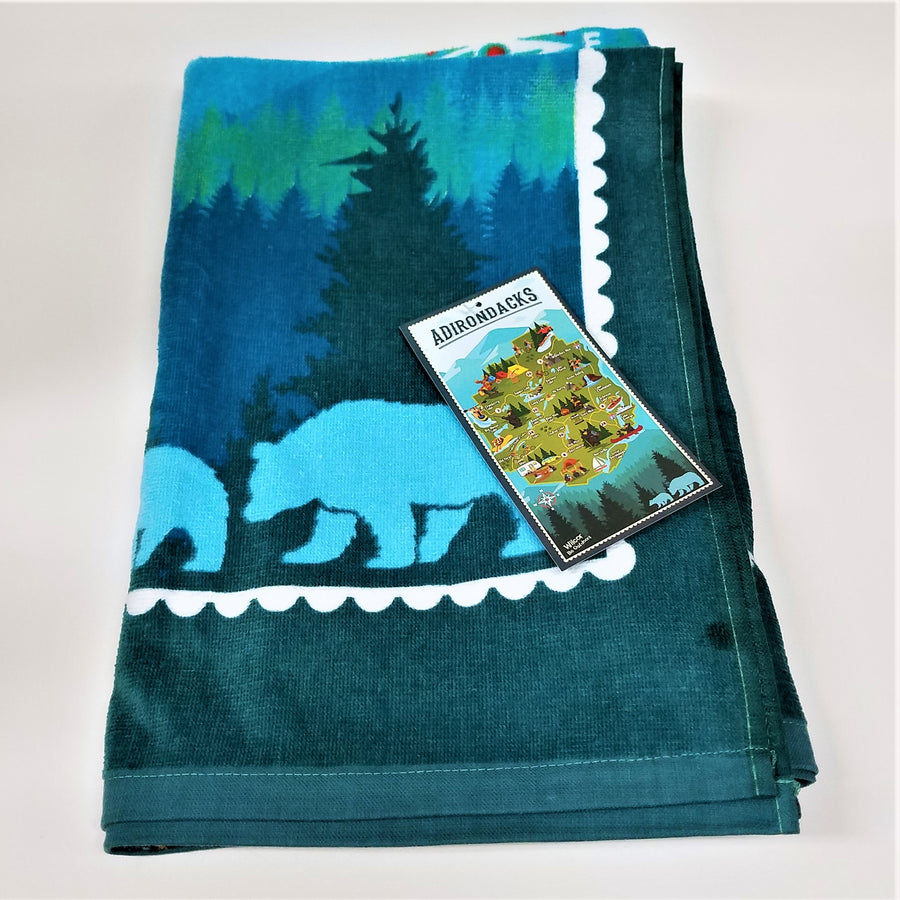 Folded portion of terry cloth towel depicting blue bears on a dark blue/green background with the manufacturer's promo tag on top