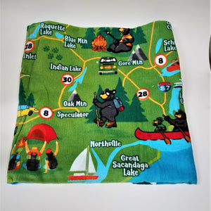 Folded terry cloth towel showing the southeast portion of the Adirondack map in greens, blues and reds with bear canoeists, and bears engaging in other Adirondack activities.