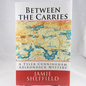 Cover of Between the Carries book by Jamie Sheffield with a map in the middle of  the book cover above the text: A Tyler Cunningham Adirondack Mystery