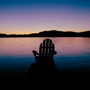 Barry Lobdell's photo card image of Adirondack chair facing water with Adirondack mountains in the distance. Sunset with purple and blue hues.