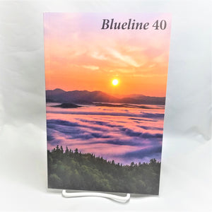 Cover of Blueline 40 book featuring a sunset over purple mountains and water with an evergreen foreground