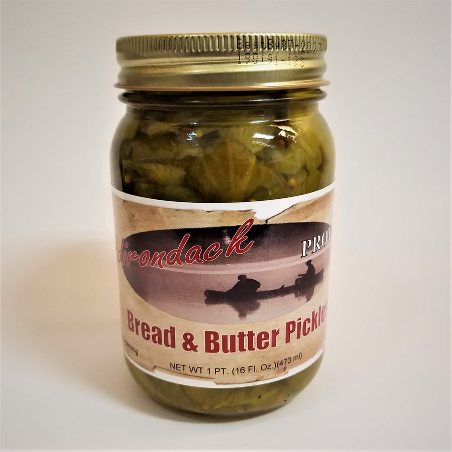 Glass jar of Bread & Butter Pickles with green pickles showing through around the label under a gold screw top.