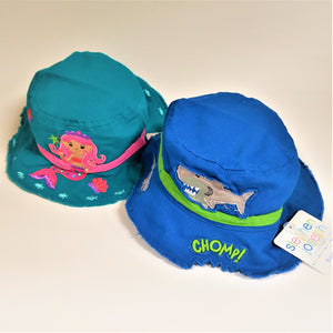Two toddler-sized bucket hats. Left qua with a pink mermaid and pink band. Right , bright blue with a green band and work CHOMP! a grey shark above that and a bite taken out of the hat under the word CHOMP!