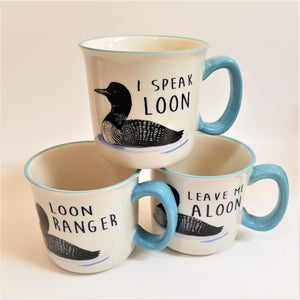 Three mug--two on bottom with one stacked center on top. All are cream-colored with a light-blue handle to the right and a light-blue rim. Each have a black and white loon print and each have a different Loon Pun printed in black letter over the back of the loon.