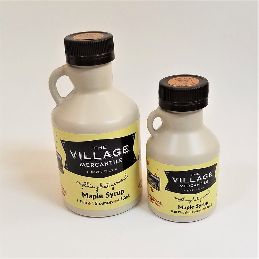 Two different sizes of maple syrup jugs. Solid jug with handle on the left, black screw top and The Village Mercantile label bottom, mid-section of each.