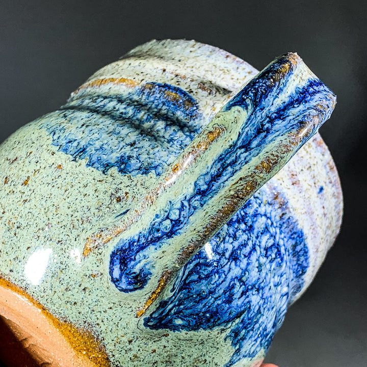 Diagonal view of ceramic mug with handle in middle. Blue speckled glaze on top left, handle and bottom right with green speckled glaze filling in elsewhere