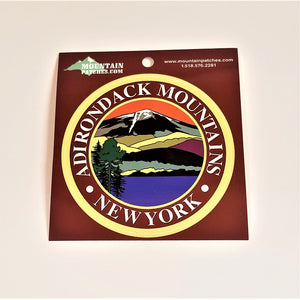 Full view of the Adirondack Mountains sticker on its brown packaging. A gold circle surrounds the white text: ADIRONDACK MOUNTAINS NEW YORK in the center circle an iconic color line art drawing of the mountains, water and evergreen.