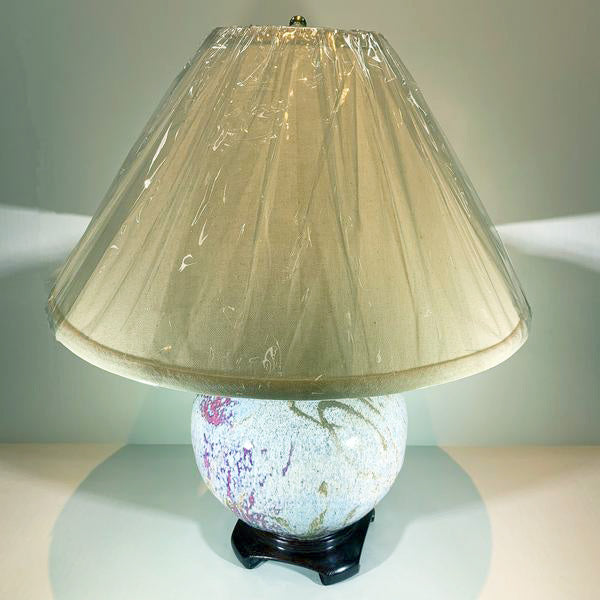 Vertical standing table lamp with black base, ceramic belly--rose and cream speckled glaze, cream-colored lampshade with plastic wrapping