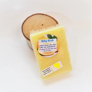 Yellow bar of Lemon Silky Sudz soap leaning on a small birch round.