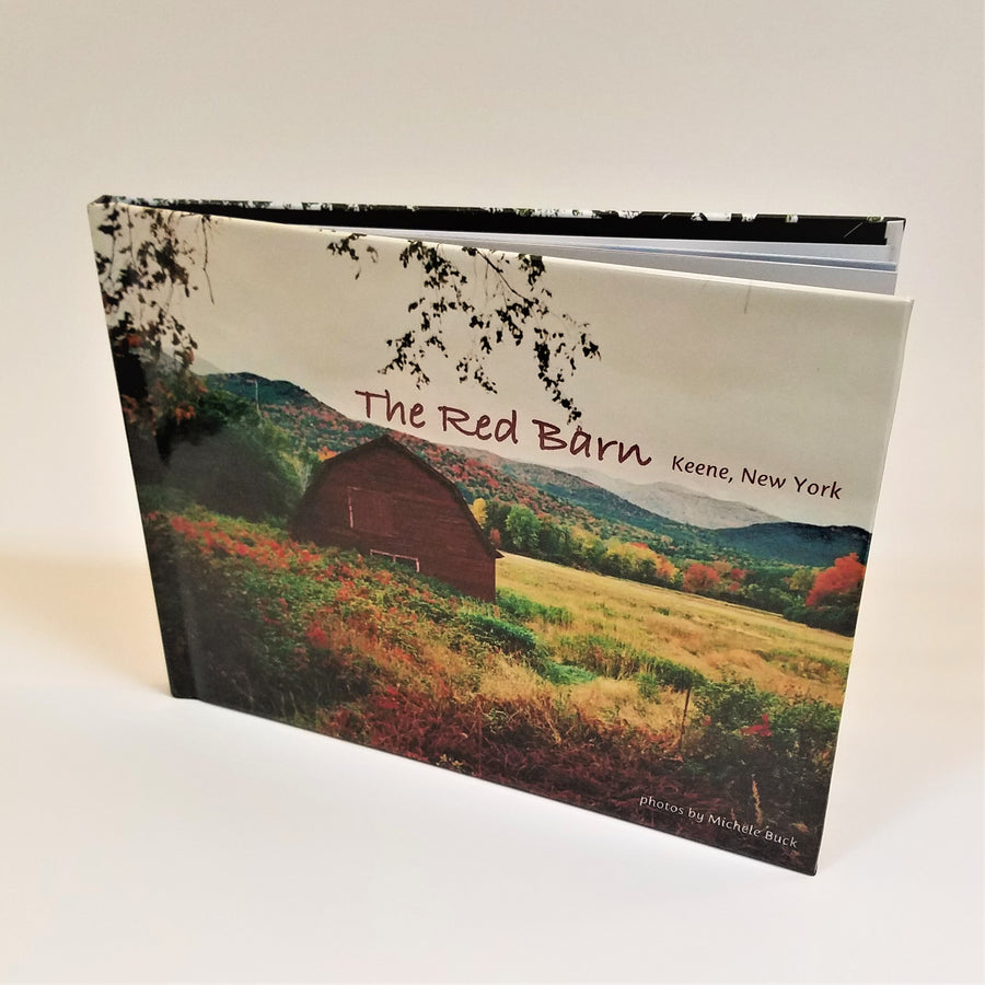 The Red Barn book standing upright with cover photo of an Adirondack autumn landscape with the Red Barn featured