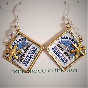 Dangling Winter Carnival square earrings. Gold band surrounds Saranac Lake Winter Carnival blue, white & black logo with small gold snowflake charm atop