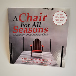 Cover of book a Chair for all Seasons puts a red Adirondack chair on a gray wooden pier set in a background of fof and water.