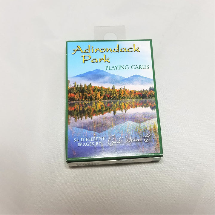 cover of boxed playing cards featuring green lettering on a blue sky atop white crested mountains, golden, green vegetation all reflected in the silver gray water.