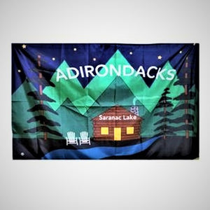 Flag opened to its full size with letters ADIRONDACKS in white type across green mountain tops and night sky over a log cabin with white text that reads Saranac Lake. The cabin's doors and windows are solid yellow. Two white Adirondack chairs sit to the left of the cabin . A ribbon of blue water is in front of the cabin with evergreens framing both sides of the flag.