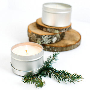 Top to bottom--silver candle tin atop 3 pieces of birch; open candle tin with lit candle atop a sprig of evergreen