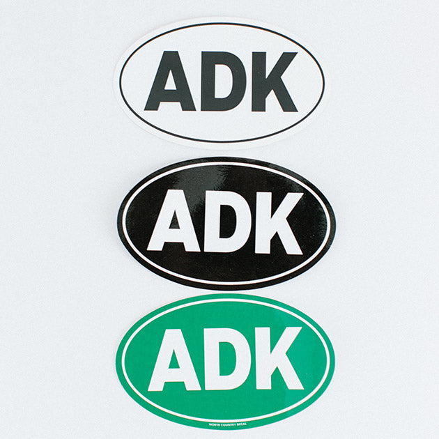 Top down, oval white sticker with black type; oval black sticker with white type; oval green sticker with white type