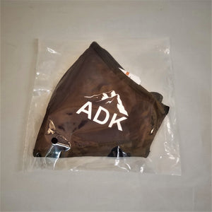 Black face mask in plastic wrap packaging. Features white type ADK lettering with a white silhouette of mountains above.