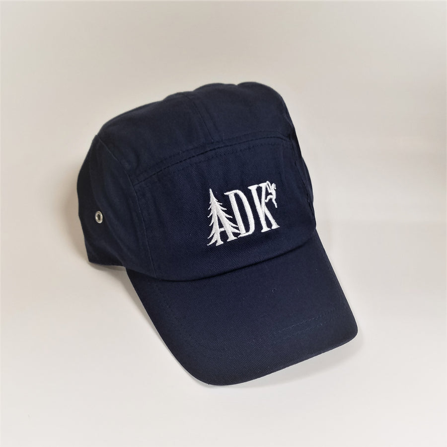 ADK panel cap in navy with white embroidery featuring the letters ADK with the A in the style of a pine tree and a small hiker climbing the top of the K