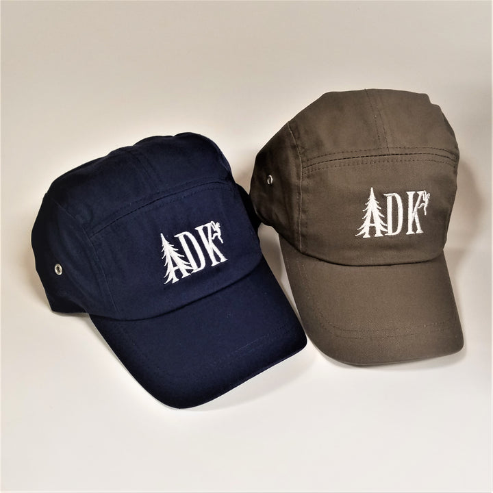 Two ADK panel caps. On the left a navy cap and to the right a brown cap. Both have white embroidery featuring  the letters ADK with the A in the style of a pine tree and a small hiker climbing the top of the K