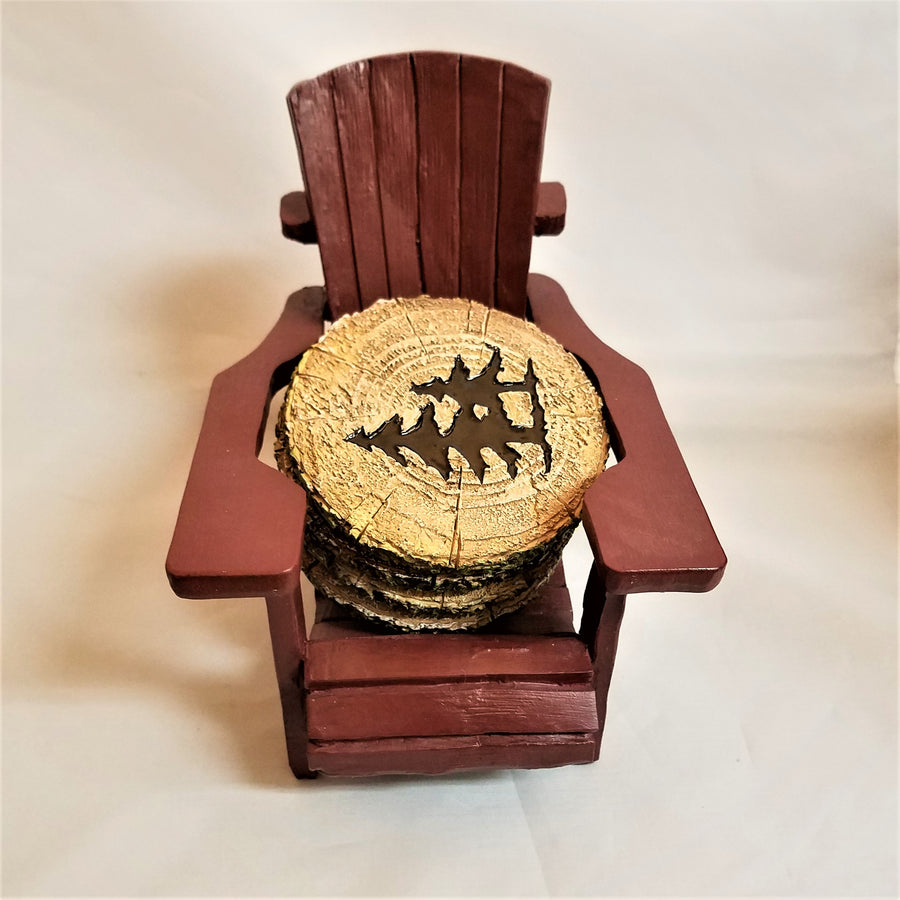 Mini maroon-colored Adirondack chair holding 4 wood-like coasters. The coaster on top is  the color of a wood core with two brown evergreens in the center.