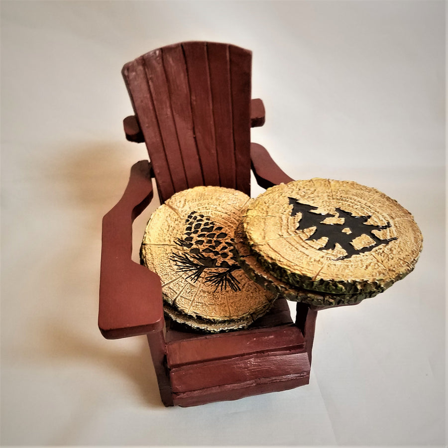 Mini maroon-colored Adirondack chair holding  coasters. The coaster leaning on chair seat depicts a brown pine cone. Two coasters rest on the chair arm. The one on top  has two brown pines in the center.