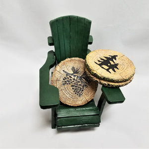 Mini green-colored Adirondack chair holding  coasters. The coaster leaning on chair seat depicts two dark green pine cones. Two coasters rest on the chair arm. The one on top  has two dark green pines in the center.