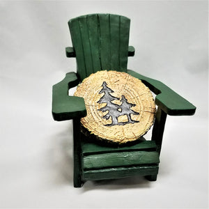 Mini green-colored Adirondack chair holding wood-like coasters. The coaster on top is the color of a wood core with two dark green evergreens in the center.