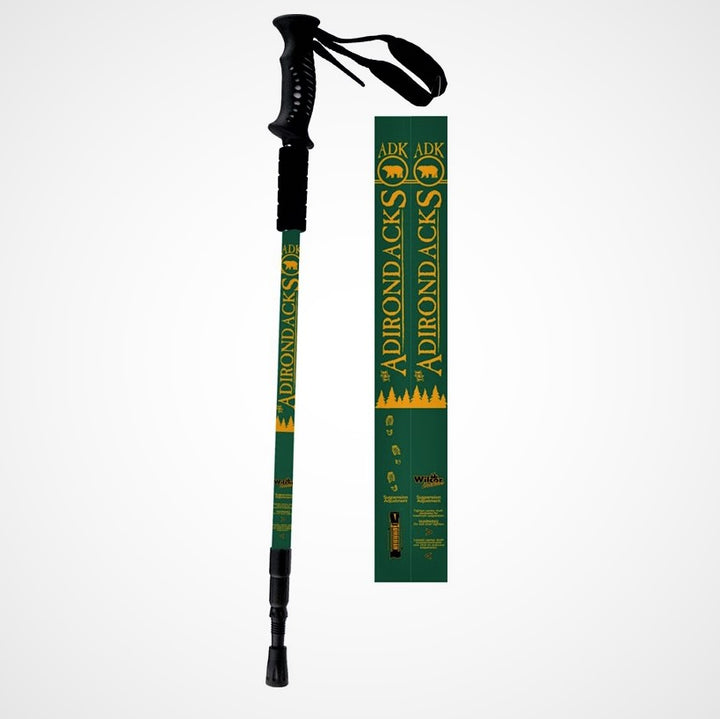Full hiking pole with black handle and strap, green body with yellow text and symbols, and black bottom. Next to the pole is a close up of the design on the stick--a green background with yellow lettering and bear in circle symbol.