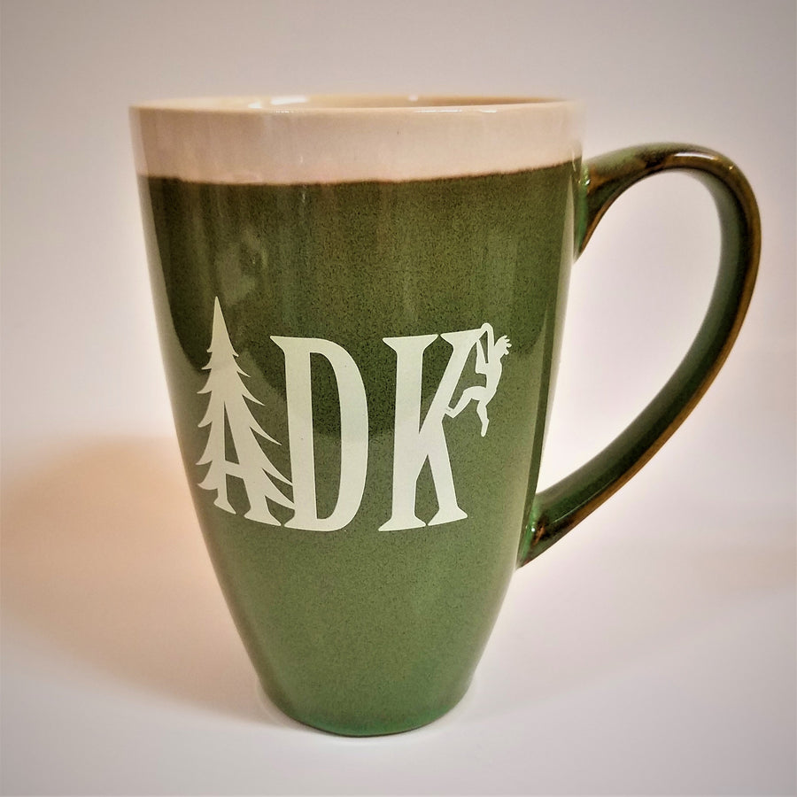 Tall green mug with whie stripe around the top with white imprint featuring the letters ADK with the A in the style of a pine tree and a small hiker climbing the top of the K.  Extra large handle visible on the right side.