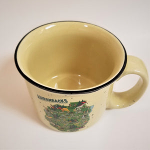 View looking down at mug with solid cream colored inside and black rim around the top. Colorful ADK park map below center on front of mug with right handle perspective.