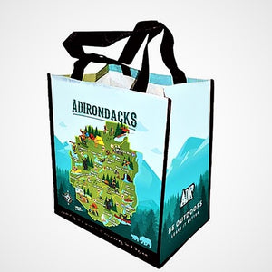 Full view of Adirondack map shopping tote. Black handles on top of a  bag in various shades of aqua and green with the word ADIRONDACKS in uppercase across the top .  The iconic green map of the Adirondack Park is in the center of mountains and trees. A directional icon and two bears rest on opposite sides on the bottom front. The side panel features mountains and forest and  white lettering: ADK BE OUTDOORS Leave It Better