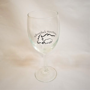 Clear wine glass with black text and black illustration of a bear, pine tree, and mountain outline.