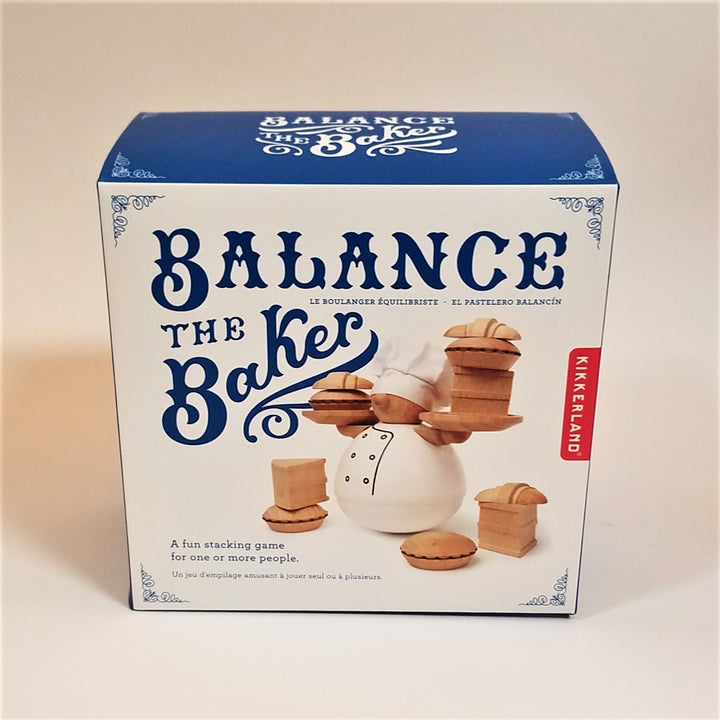 Blue and white box stands upright with Balance the Baker in blue typo next to and above a photo of the rounded baker holding tiny wooden pies and plates surrounded and 3 sets of wooden baked goods positioned around round baker bottom.