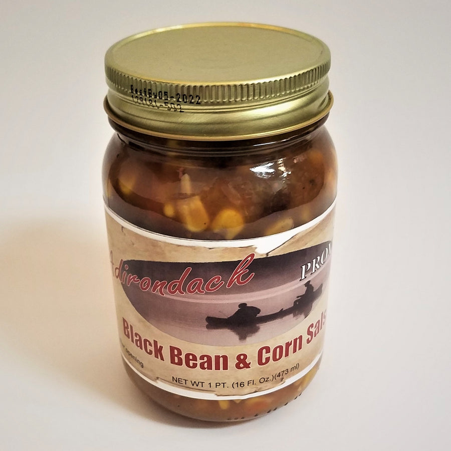 Glass jar of Black Bean & Corn Salsa. Yellow corn and a glimpse of black bean can be seen through the glass under the gold screw top.