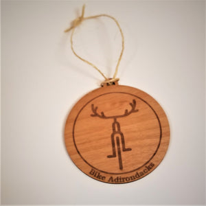 Faux wood round ornament with brown bicycle icon with antler-like handlebars within a brown circle. Below the circle in brown type are the words Bike Adirondacks.  A thin-rough cord is attached to the top for hanging.