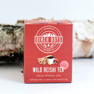 Red box of Birch Boys Wild Reishi Tea standing upright in front of a birch log.