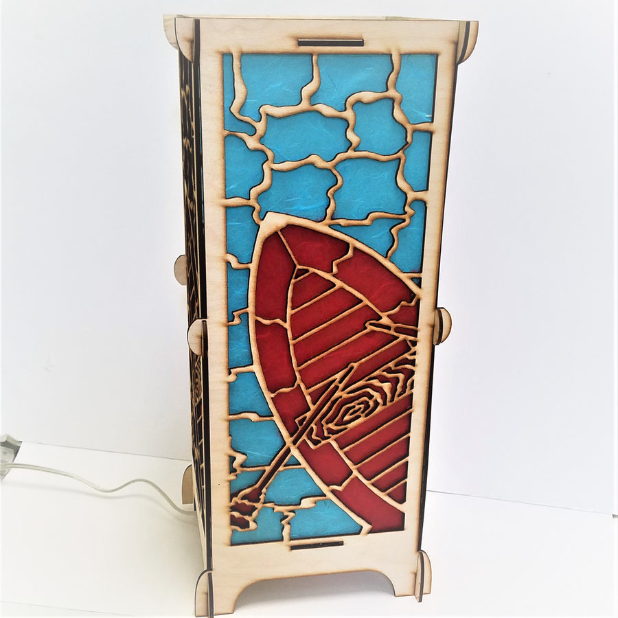 Art lamp standing straight up with showing full panel of boat and oar in red with wood outline and blue water surrounding, glimpse of side panel and white electric cord.