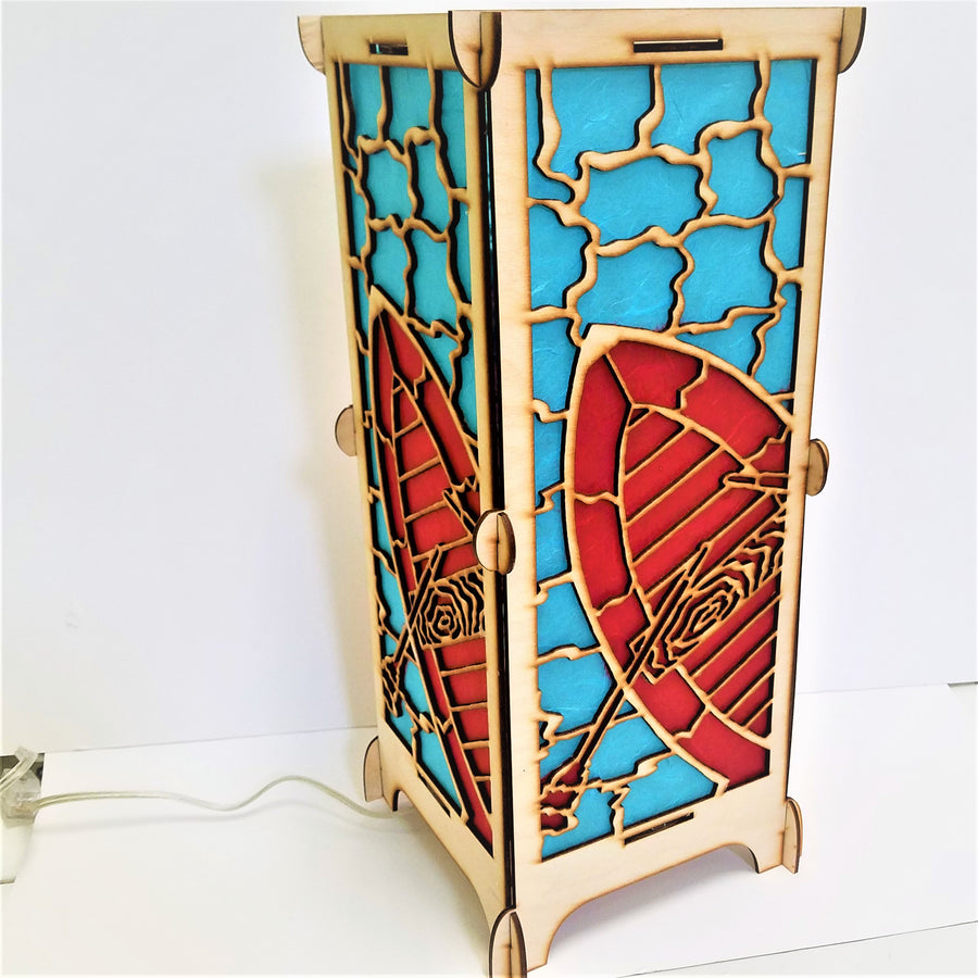 Art lamp standing straight up revealing two panels of the four-sided lamp. Red boat and oars, blue water and light wood creating the outlines and overall structure. Cord comes from bottom and extends to the left.