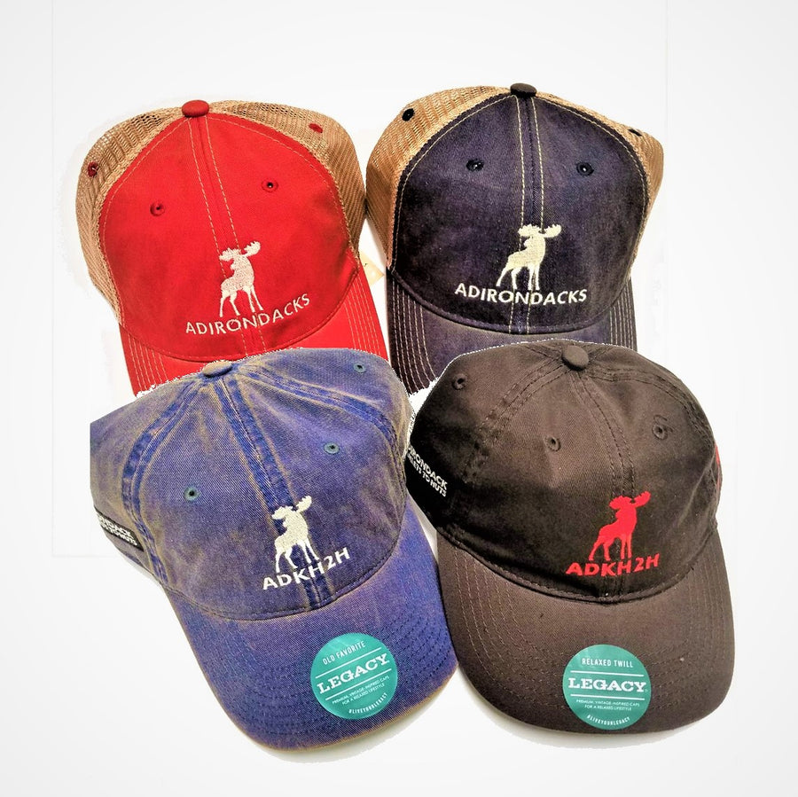Four caps--from left to right back row--red with khaki mesh back and white moose and white Adirondacks lettering; to the right blue fronted cap with khaki mesh back and white moose and white Adirondacks lettering; front left pre-washed looking blue cap with white moose in front and white lettering ADKH2H with green round label on brim, front right--pre-washed looking brown cap with red moose in front and red lettering ADKH2H with green round label on brim,